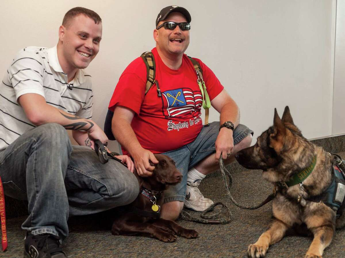Ottmar Klass / STRIDE Adaptive Sports Jeremy Walton of Castleton sits with his new service dog, Alanna, as Timothy McDonough of Spokane, Wash, formerly of Germantown, sits with his service dog, Bailey, at the Albany International Airport in Albany.
