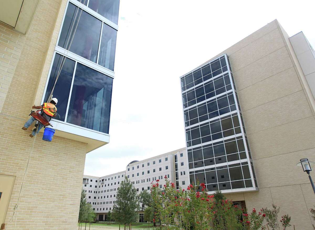 A window washer works on the windows of Cougar Village II, one of two UH dorms where freshmen may be required to spend their first year.