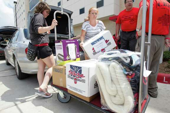 U of H freshmen Hannah Patterson, left ,and Sister Kristy Parson unpack  during move in day at Cougar Village II on Thursday, Aug. 22, 2013, in Houston.