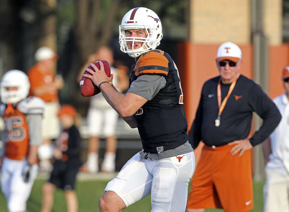 David Ash throws under the watchful eye of coach Mack Brown, who has handed the reins to the confident junior quarterback. Photo: Tom Reel / San Antonio Express-News