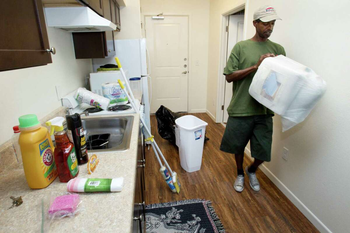 Clarence Brown, an Air Force veteran living at Travis Street Plaza, unpacks the welcome basket given to him Friday, Aug. 23, 2013, in Houston. Adopt-A-Vet dipped off 116 welcome baskets filled with basic household items.