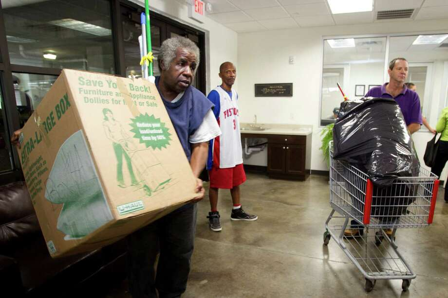 Lawrence Sheffield, a Navy veteran living at Travis Street Plaza, left, and Gary Benoit, far right, help carry welcome baskets into the complex Friday, Aug. 23, 2013, in Houston. Adopt-A-Vet dipped off 116 welcome baskets filled with basic household items to veterans living at Travis Street Plaza. Photo: Brett Coomer, Houston Chronicle / © 2013 Houston Chronicle