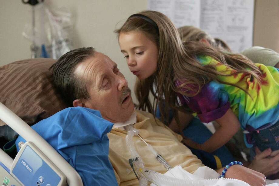 """Critically ill and breathing with a ventilator, Harrison County Deputy Michael Freeman gets a kiss from his granddaughter Hallie, who refers to him as """"Papa."""" Photo: Johnny Hanson, Staff / © 2013  Houston Chronicle"""