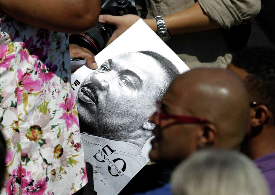 A woman carries a sign with the image of Martin Luther King Jr. on it through the crowd during an event to commemorate the 50th anniversary of the 1963 March on Washington at the Lincoln Memorial, Saturday, Aug. 24, 2013, in Washington. Photo: Carolyn Kaster, Associated Press / AP