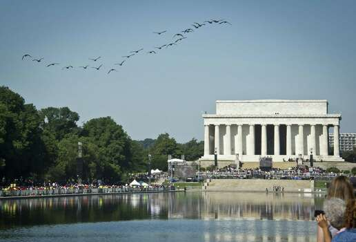 "Wild geese fly over the reflecting pool near the Lincoln Memorial while thousands of people gather to commemorate the 50th anniversary of the March on Washington and Dr. Martin Luther King, Jr.'s ""I have a Dream"" speech on August 24, 2013, in Washington, DC. Photo: MLADEN ANTONOV, AFP/Getty Images / AFP"