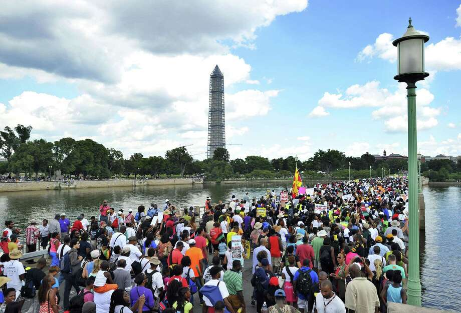 "People take part in a march on August 24, 2103, in Washington, DC, commemorating the 50th anniversary of The March on Washington. Tens of thousands gathered on August 24 to mark 50 years since the March on Washington, the civil rights watershed where Martin Luther King Jr famously declared: ""I have a dream."" The March on Washington is best remembered for King's stirring vision of a United States free of inequality and prejudice, telecast live to a nation undergoing a phenomenal decade of soul-searching, crisis and change. Photo: JEWEL SAMAD, AFP/Getty Images / AFP ImageForum"