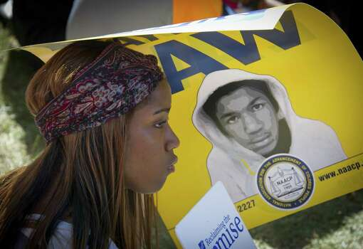"A girl holds a poster of Trayvon Martin as thousands gather to commemorate the 50th anniversary of the March on Washington and Dr. Martin Luther King, Jr.'s ""I have a Dream"" speech on August 24, 2013, near the Lincoln Memorial in Washington, DC. Photo: MLADEN ANTONOV, AFP/Getty Images / AFP"
