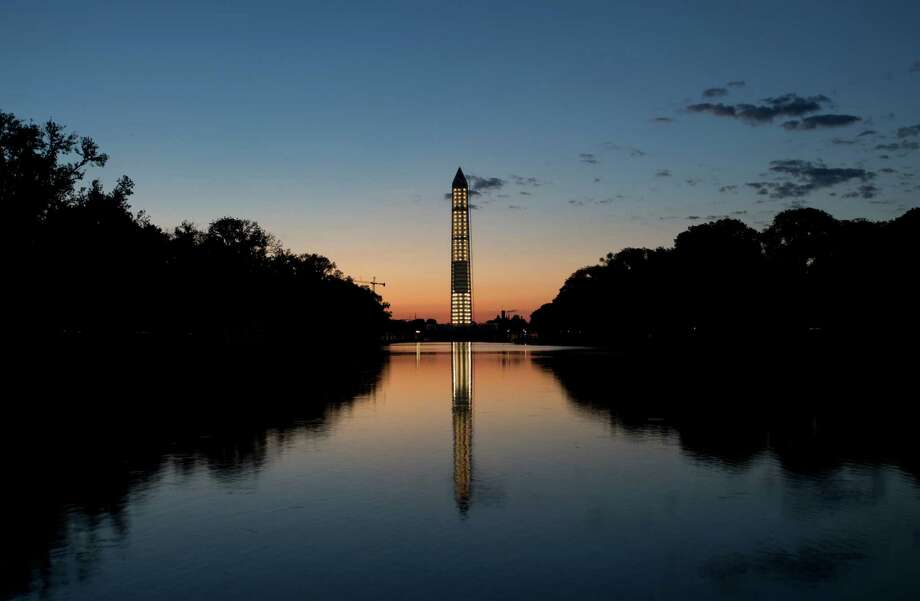 The Washington Monument is mirrored in the Reflecting Pool just before sunrise before an event to commemorate the 50th anniversary of the 1963 March on Washington at the Lincoln Memorial, Saturday, Aug. 24, 2013, in Washington. Photo: Carolyn Kaster, Associated Press / AP