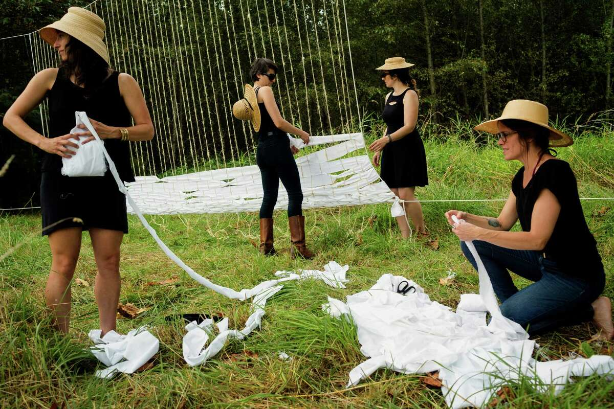"""Artists weave together the """"Done/Undone"""" loom installation at the seventh annual Lo-Fi Festival Saturday, August 24, 2013, at The Smoke Farm in Arlington. This year's theme was """"Must Be Present to Win!"""""""