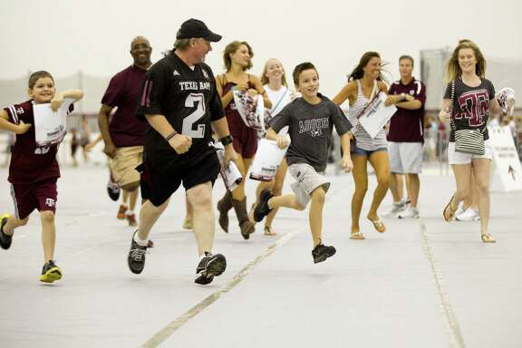 The race is on as Texas A&M fans run to get in line to get an autograph from quarterback Johnny Manziel on Saturday.