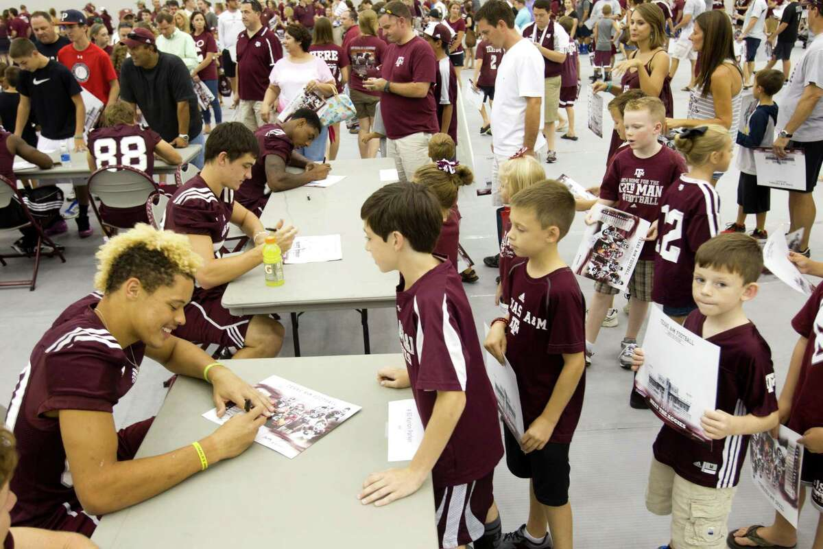 """Texas A&M receiver Kyrion Parker, left, gets a kick out of signing autographs for young fans during """"Meet the Aggies"""" on Saturday in College Station."""