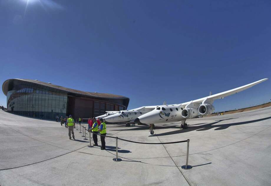 Virgin Galactic's jet-powered carrier aircraft WhiteKnightTwo sits in front of the Spaceport America hangar in Upham, N.M., in 2011. Virgin Glactic hopes to get civilians into space soon. Photo: Matt York / Associated Press