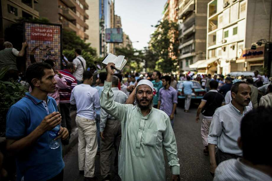 A demonstrator holds up a Quran during a protest Saturday against the military-backed government in the Muhandisin neighborhood of Cairo. Photo: Bryan Denton / New York Times