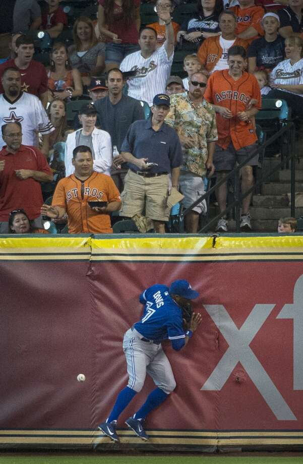 Blue Jays right fielder Rajai Davis collides with the wall as he tries to make the play on a double by Astros left fielder L.J. Hoes. Photo: Smiley N. Pool, Houston Chronicle