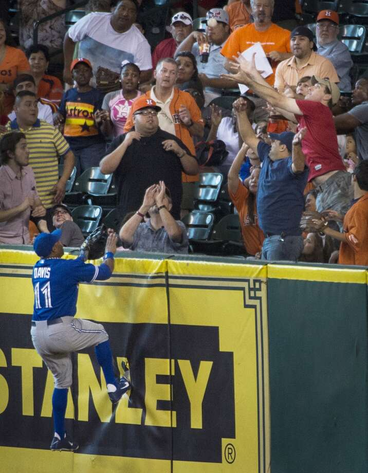 Blue Jays right fielder Rajai Davis climbs the wall only to watch a home run off the bat of Astros catcher Jason Castro land in the seats. Photo: Smiley N. Pool, Houston Chronicle