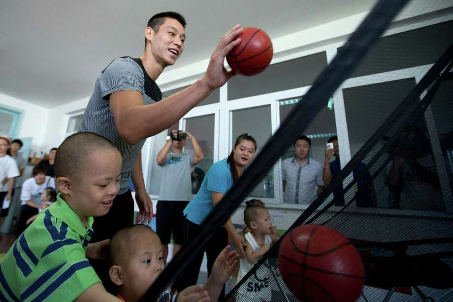 Rockets guard Jeremy Lin provides a shooting lesson during his visit to an orphanage for children with congenital illnesses such as cerebral palsy in Tianjin, China. Photo: Alexander F. Yuan, STF / AP