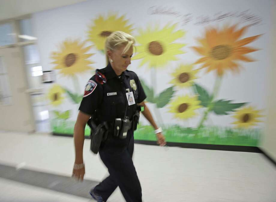 A school resource officer walks the hallways in Pembroke Pines, Fla. Many schools are putting officers on permanently after the school shootings in Newtown, Conn. Photo: Wilfredo Lee / Associated Press