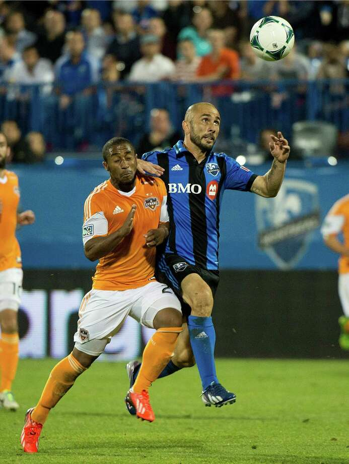 Montreal Impact's Marco Di Vaio, right, and Houston Dynamo's Corey Ashe battle for the ball during the second half of an MLS soccer game in Montreal, Saturday, Aug. 24, 2013. (AP Photo/The Canadian Press, Graham Hughes) Photo: Graham Hughes, Associated Press / The Canadian Press
