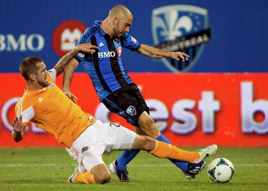 Montreal Impact's Marco Di Vaio, right, and Houston Dynamo's Eric Brunner battle for the ball during the second half of an MLS soccer game in Montreal, Saturday, Aug. 24, 2013. (AP Photo/The Canadian Press, Graham Hughes) Photo: Graham Hughes, Associated Press / The Canadian Press