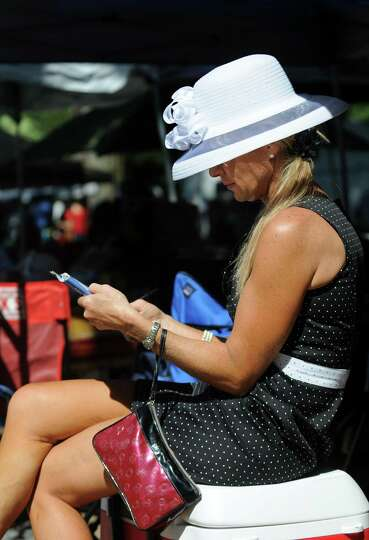 Equine veterinarian Tania Woerner of Middleburg, Va. looks over the races scheduled for Travers Day