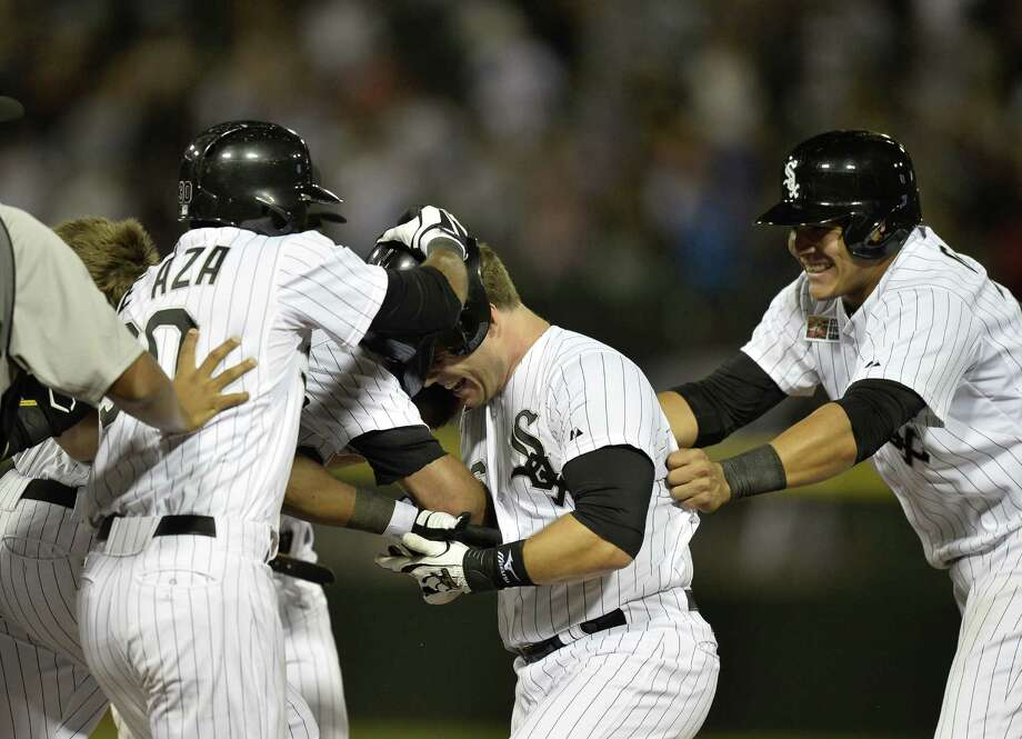 Josh Phegley (center) of the White Sox is mobbed by teammates after his gamewinning, RBI single in the ninth inning. Photo: Brian Kersey / Getty Images