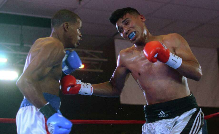 Luis Torres, right, lands a body shot on Miguel Pizarro during a pro-am boxing card at the San Antonio Events Center on Saturday, Aug. 24, 2013. Torres won the fight. Photo: San Antonio Express-News / San Antonio Express-News