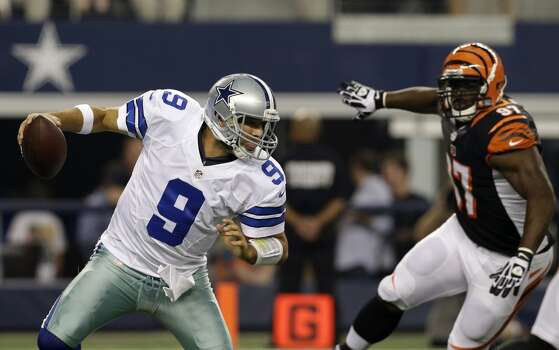 Dallas Cowboys quarterback Tony Romo (9) scrambles away from pressure by Cincinnati Bengals' Geno Atkins (97) during the first half of an preseason NFL football game, Saturday, Aug. 24, 2013, in Arlington, Texas. (AP Photo/LM Otero) Photo: Associated Press