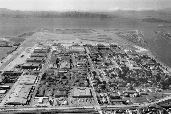 Aerial view of Alameda Naval Air Station. The Bay Bridge and the S.F. skyline are visible in the background. March 11, 1993.