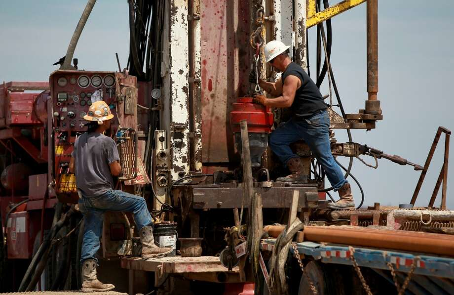 Driller Paul Allison (left) and tool pusher Ron Hawkins (right) prepare to add another 30 foot section of pipe at the independent Barrett Brothers Number 1 drilling rig in Presidio County between Alpine and Marfa, Texas. Photo: JOHN DAVENPORT, SAN ANTONIO EXPRESS-NEWS