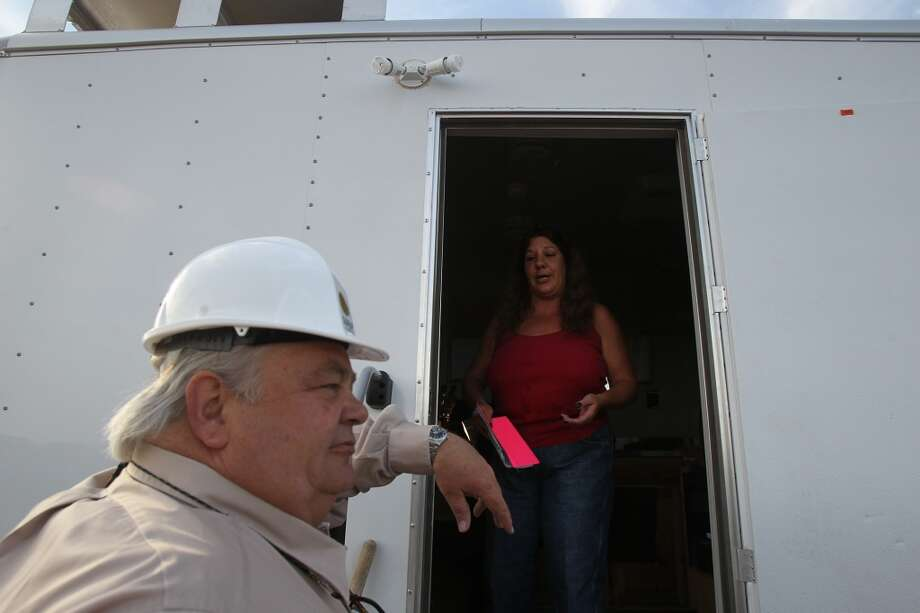 Land man and project partner Jimmy Nixon (left) talks with drilling rig mud logger Tish McGee at a trailer at the site of the Barrett Brothers Number 1 drilling rig between Marfa and Alpine, Texas. A mud logger keeps detailed records of a well's bore hole by examining the cuttings of rock brought to the well's surface. Photo: JOHN DAVENPORT, SAN ANTONIO EXPRESS-NEWS
