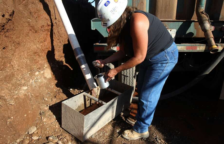 Barrett Brothers number 1 drilling rig mud logger Tish McGee gathers bore hole samples that she will later examine under a microscope. The rig is located in Presideo County between Marfa and Alpine, Texas. Photo: JOHN DAVENPORT, SAN ANTONIO EXPRESS-NEWS