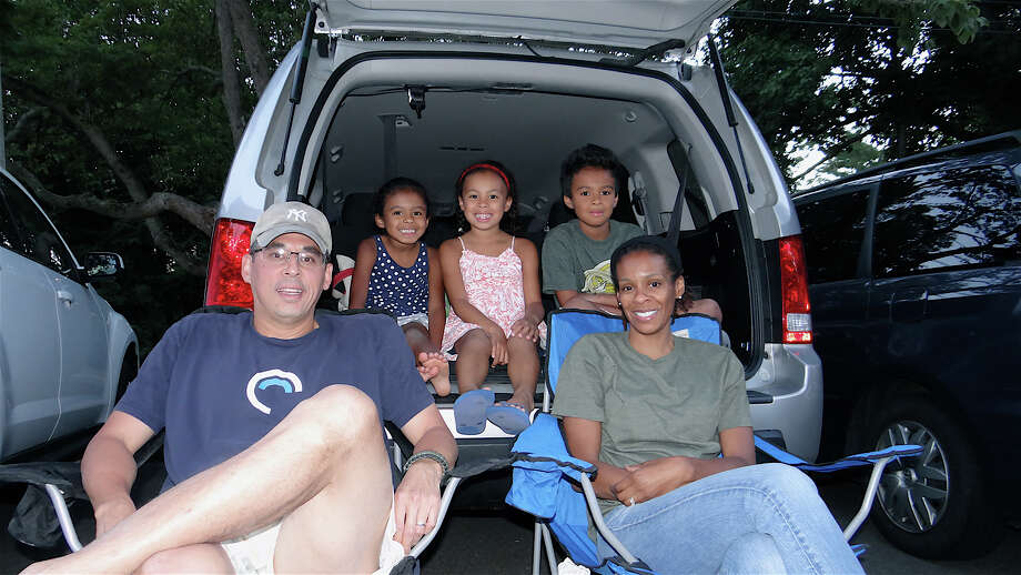 "Jeff Oh of Southport and his family Campell, Morgan, Logan and Traci gathered at the back of their van Saturday night to watch ""Finding Nemo,"" the featured film at Trinity Episcopal Church's Drive-In Night. Photo: Mike Lauterborn / Fairfield Citizen contributed"