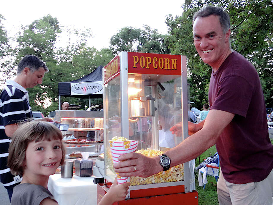 Trinity Episcopal Church member Jim Funk passes popcorn to Anna Billy, 6, of Fairfield at the church's Drive-in Movie Night event Saturday night. Photo: Mike Lauterborn / Fairfield Citizen contributed
