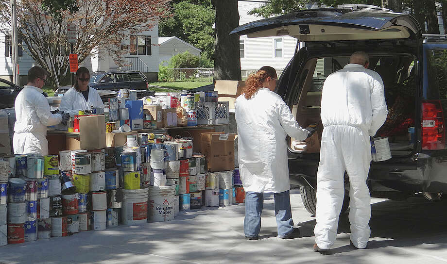 Clean Harbors workers remove hazardous household materials from a vehicle at the town-organized collection of hazardous wastes Saturday at Veterans Park. Photo: Mike Lauterborn / Fairfield Citizen contributed