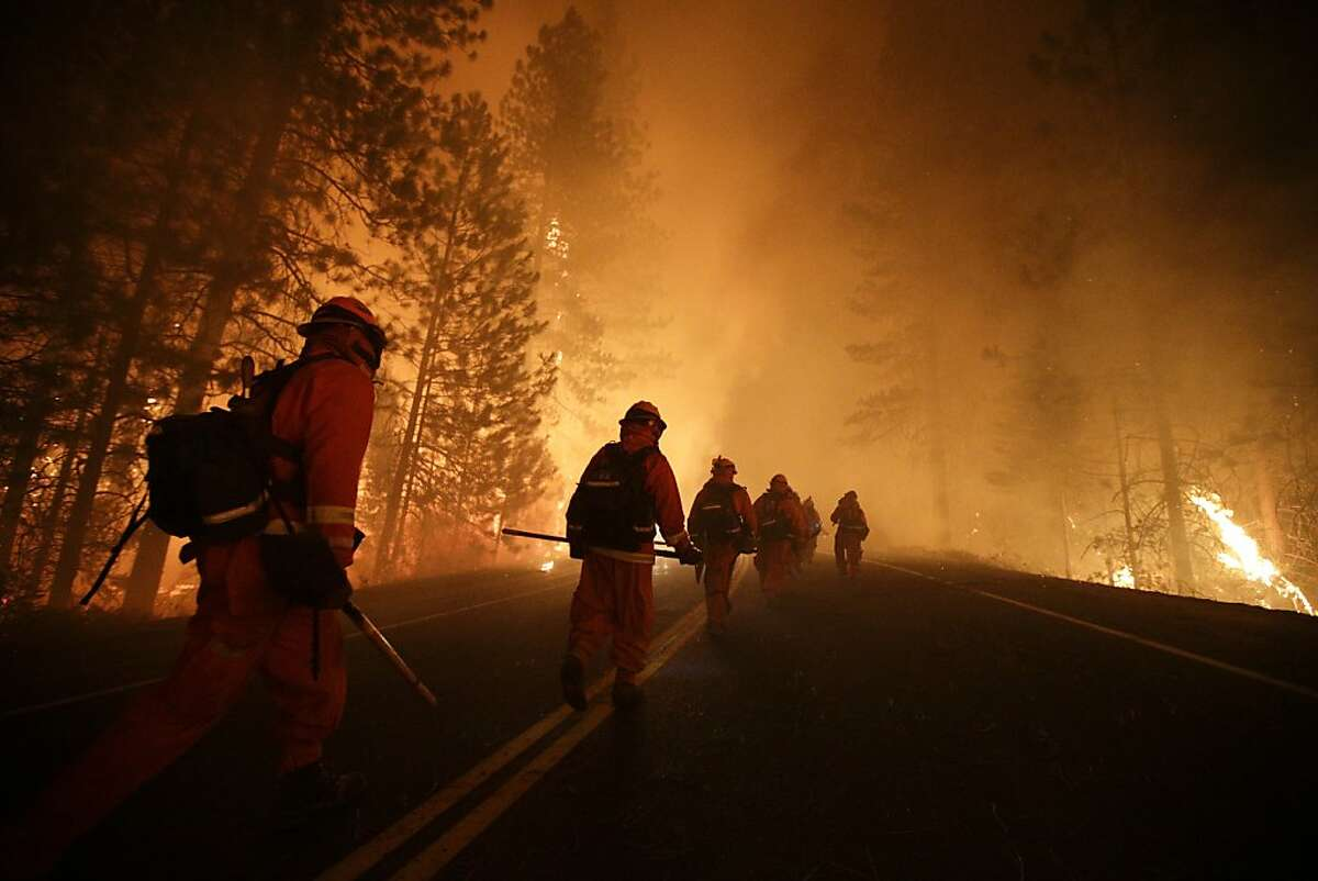 Inmate firefighters walk along state Highway 120 as firefighters continue to battle the Rim Fire near Yosemite National Park, Calif., on Sunday, Aug. 25, 2013. Fire crews are clearing brush and setting sprinklers to protect two groves of giant sequoias as a massive week-old wildfire rages along the remote northwest edge of Yosemite National Park. (AP Photo/Jae C. Hong)
