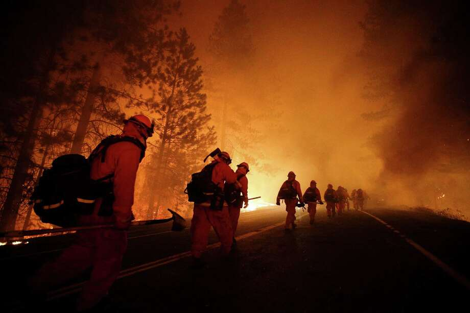 Inmate firefighters walk along Highway 120 after a burnout operation as firefighters continue to battle the Rim Fire near Yosemite National Park, Calif., on Sunday, Aug. 25, 2013. Fire crews are clearing brush and setting sprinklers to protect two groves of giant sequoias as a massive week-old wildfire rages along the remote northwest edge of Yosemite National Park. Photo: AP