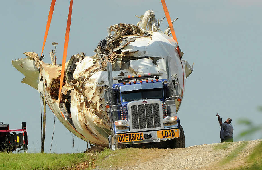 Workers load the fuselage wreckage of the UPS plane that crashed last week in a field north of the Birmingham-Shuttleworth International Airport, Thursday, Aug. 22, 2013. The front of the fuselage is being loaded on a flat bed trailer with a huge crane. Photo: AP