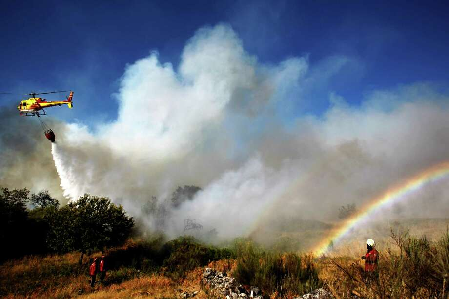 Portuguese firefighters work as a helicopter sprays water to extinguish a fire in Adsamo, near Vouzela, Portugal, Friday, Aug. 23, 2013. More than 600 Portuguese firefighters were battling six new wildfires a day after one firefighter was killed and nine others injured when gusting winds caused a fire to change direction. Portugal's National Civil Protection agency said water-bombing planes were also being used to fight fires Friday in north-central Portugal. Photo: AP