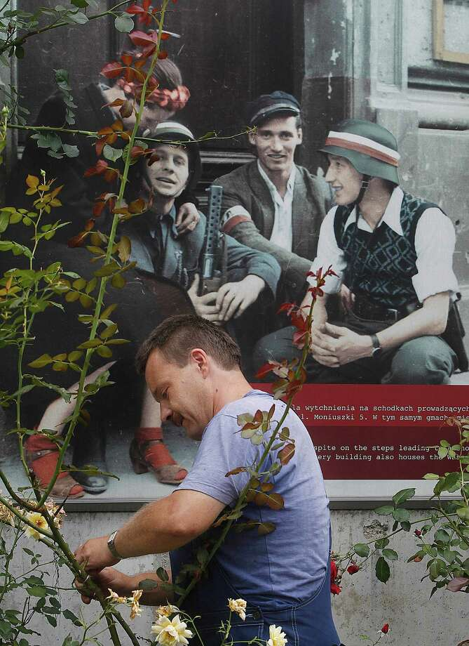 "In this picture taken Tuesday, Aug. 13, 2013, a man working in the Park of Freedom at the Warsaw Rising Museum in Warsaw, Poland, that is decorated with recently colored historical pictures that were taken during the city's 1944 revolt against the occupying Nazi Germans. Museum historians and cinematographers have made a unique ""Warsaw Rising"" feature movie by coloring and adding sound and a story line to the black-and-white silent historical film reels taken during the doomed revolt by the clandestine Home Army cameramen. The movie is to hit cinemas in Poland and abroad next year. Photo: AP"