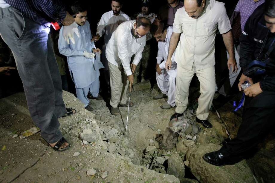 Pakistani investigators examine the site of bombing in Karachi, Pakistan, Thursday, Aug. 22, 2013. A roadside bomb hit a convoy of security forces in the southern city of Karachi on Thursday night, killing one person and wounding 20 others, said police official Ishtiaq Ahmed. No one has claimed responsibility for the attack, but suspicion likely will fall on the Taliban. Photo: AP