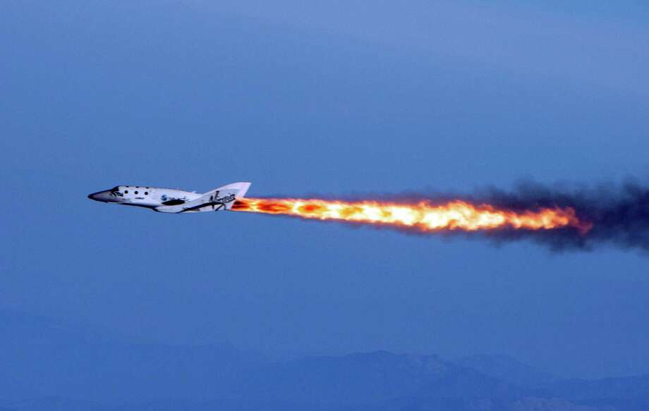 "In this April 29, 2013 photo provided by Virgin Galactic, the company's SpaceShipTwo fires its rockets over Mojave, Calif. after it was dropped from its ""mothership,"" WhiteKnightTwo. It is one of several new private ventures that involve taking people into outer space for a price, ventures that many hope will become as lucrative as they are revolutionary. And that prospect has California racing other states to woo new space companies with cushy incentives. Photo: AP"