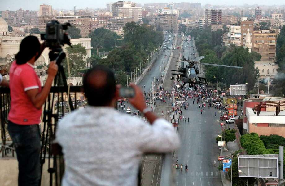 In this Friday, July 5, 2013 file photo, journalists film an Egyptian military attack helicopter flies by the Presidential palace, in Cairo, Egypt.  An Egyptian journalist shot to death by soldiers at a checkpoint raises to five the number of journalists killed in the past week across Egypt. There has also been an dramatic escalation of harassment of foreign journalists, ignited by the perception that the Western media's coverage of events in Egypt has been biased against the military. Local media have also fueled tensions, acting less as watchdogs of government and instead building support for the new military-backed government. Lost is truth of how events unfolded, making accuracy the latest casualty of the turmoil. Photo: AP