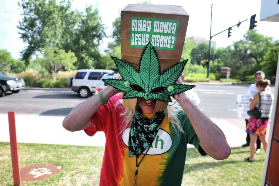A medical marijuana patient wears a paper bag over his head during a protest against alleged state government security breaches, in Denver, Wednesday Aug. 21, 2013. Protesters asked Colorado health authorities to completely dismantle the state's 107,000-person marijuana patient registry because of what they call breaches of private medical information. Photo: AP