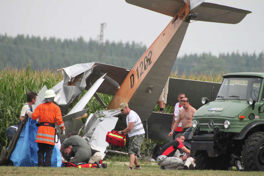Firefighters and rescuers stand next to a crashed plane in Tannheim, Germany Saturday Aug. 24, 2013. Police say one person was severely injured at a flight event in southern Germany when a vintage biplane crashed during takeoff. Police spokesman Reinhold Ruf said the accident happened Saturday at the annual Tannkosh flight festival near Biberach when the plane  came off the runway and then crashed into another plane that was parked nearby. A 65-year-old man was severely injured and had to be taken to the hospital by helicopter. Ruf said two more people were slightly injured. Photo: AP