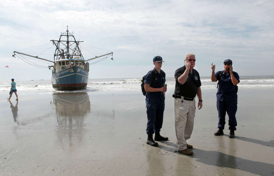 Tom Foley, Atlantic City's Emergency Management Coordinator, center, speaks with Coast Guard members where a beached fishing vessel sits stranded in Atlantic City, N.J.,  Monday, Aug. 19, 2013. The Jessica Heather, a 56-foot fishing boat, has run aground near Caesar's Pier in Atlantic City. Photo: AP