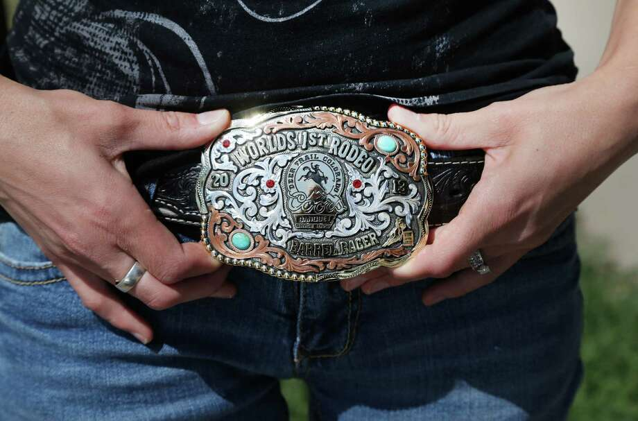 Local waitress Mindy Miller shows off her award belt buckle on Thursday Aug. 22, 2013, won a week earlier for barrel racing at her hometown rodeo in Deer Trail, Colo. This rural town an hour east of Denver that calls itself home of the world's first rodeo has an unusual special election coming up in October: Should the city issue hunting licenses to shoot down unmanned aerial drones? Photo: AP