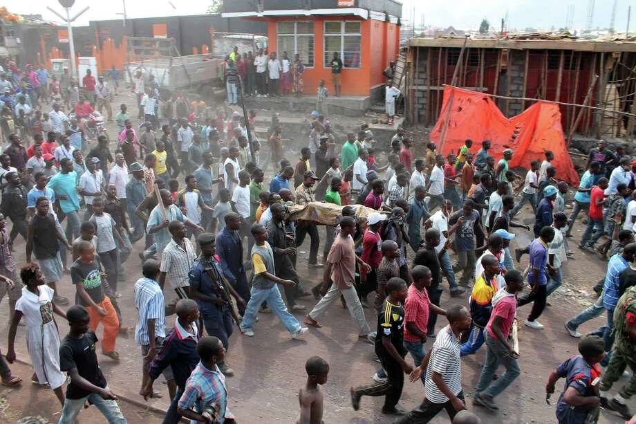 Angry residents carry the body of a person killed hours earlier when a rocket struck a home, as they take to the streets in protest over recent violence, in Goma, Congo, Saturday, Aug. 24, 2013. Congolese soldiers supported by U.N. forces fought rebels in the country's deteriorating east for hours early Saturday, officials said, while a rocket landed inside the town of Goma. Congo immediately blamed the attacks on neighboring Rwanda, which has long been accused of supporting the eastern Congolese rebel movement known as M23. Photo: AP