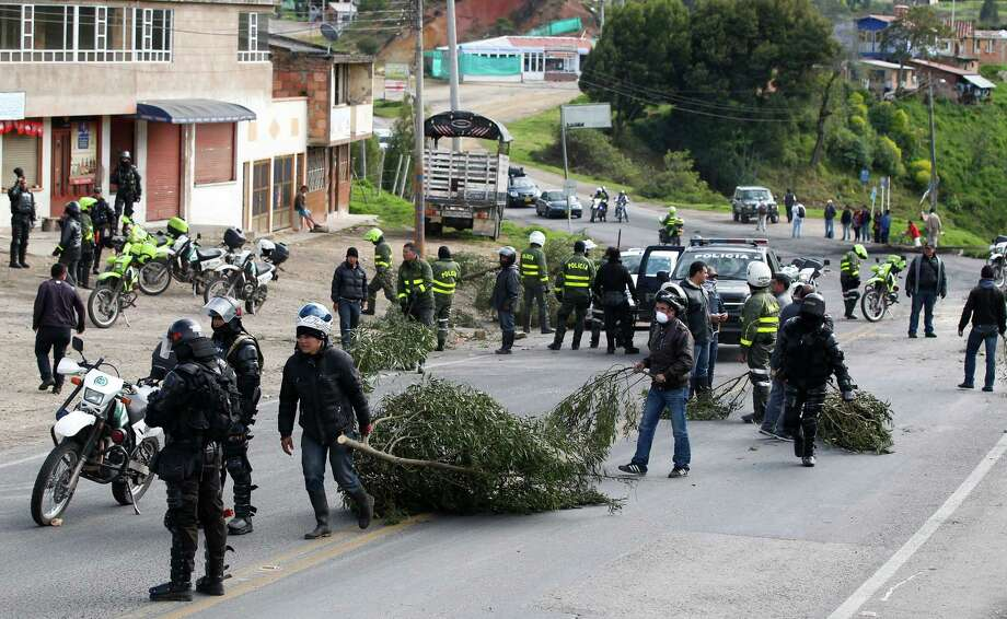 Police officers clears a barricade set by protesters in Ventaquemada, central Colombia, Thursday, Aug. 22, 2013. Farmers and truckers are blockading Colombian highways for a fourth day for an assortment of demands that include reduced gasoline prices, increased subsidies and the cancellation of free trade agreements. Photo: AP