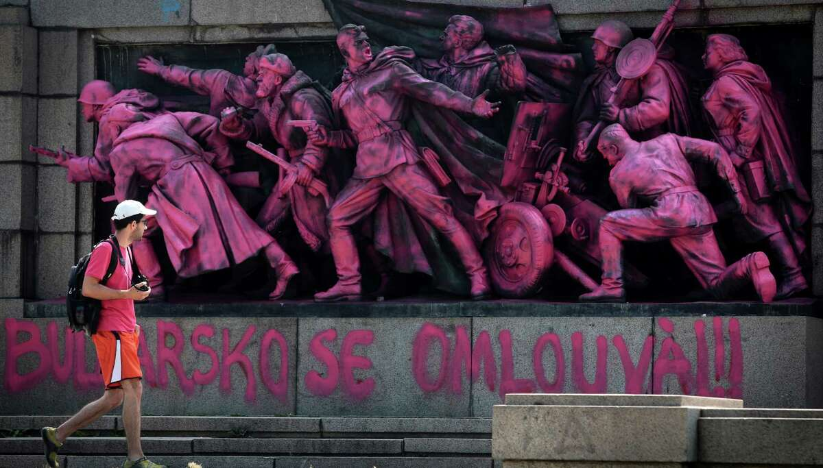 A person walks past a Soviet Army monument colored pink by unknown people to mark the anniversary of the Prague Spring with an inscription in Bulgarian and Czech below reading