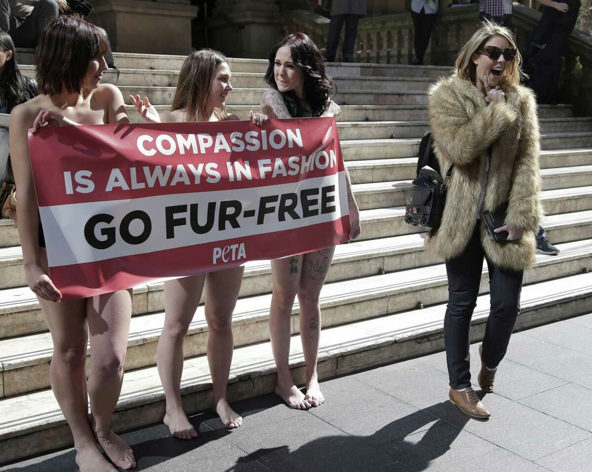 A passer-by, right, appears to mock anti-fur protesters Tanya Ward, left, Zoe Crawford and Jacqui House, right, who have stripped to their underwear in an attempt to persuade clothing designers to stop using animal fur in Sydney, Australia, Wednesday, Aug. 21, 2013. The protestors from PETA, People for the Ethical Treatment of Animals, are protesting at Sydney Town Hall where a fashion festival is set to begin.